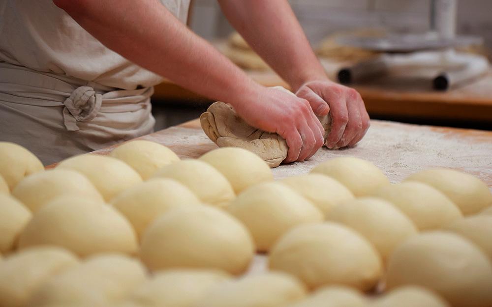 Bäcker beim Teig kneten