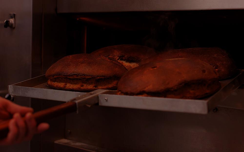 Frisch gebackene Brote auf dem Backblech abgedunkelt