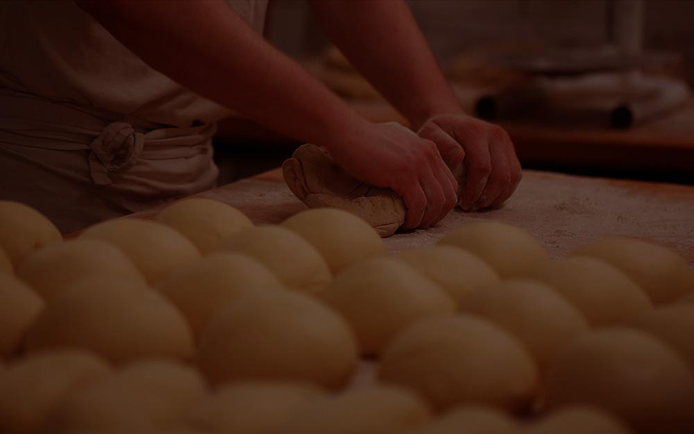 Bäcker beim Teig kneten abgedunkelt