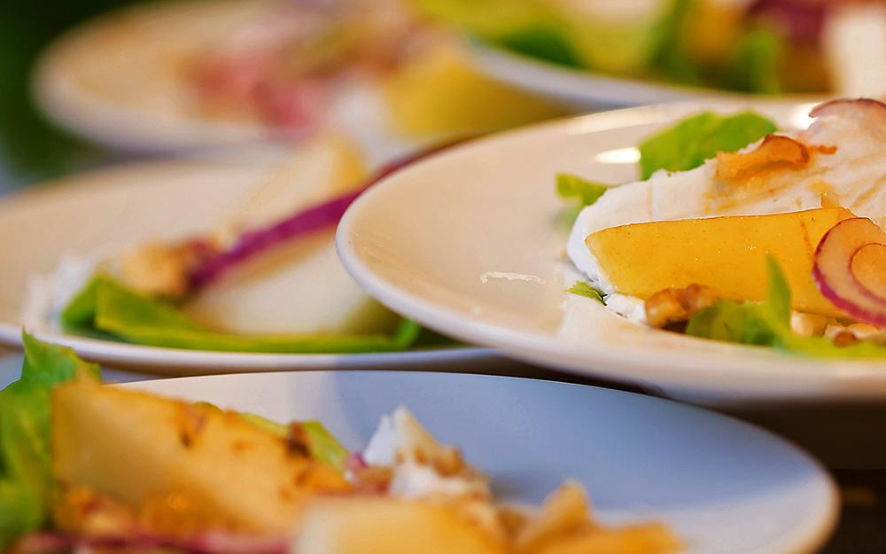 Teller mit Frischkäse und Obst auf Salat
