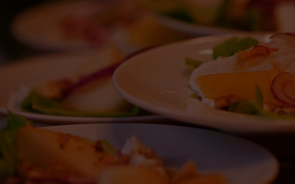 Teller mit Frischkäse und Obst auf Salat abgedunkelt
