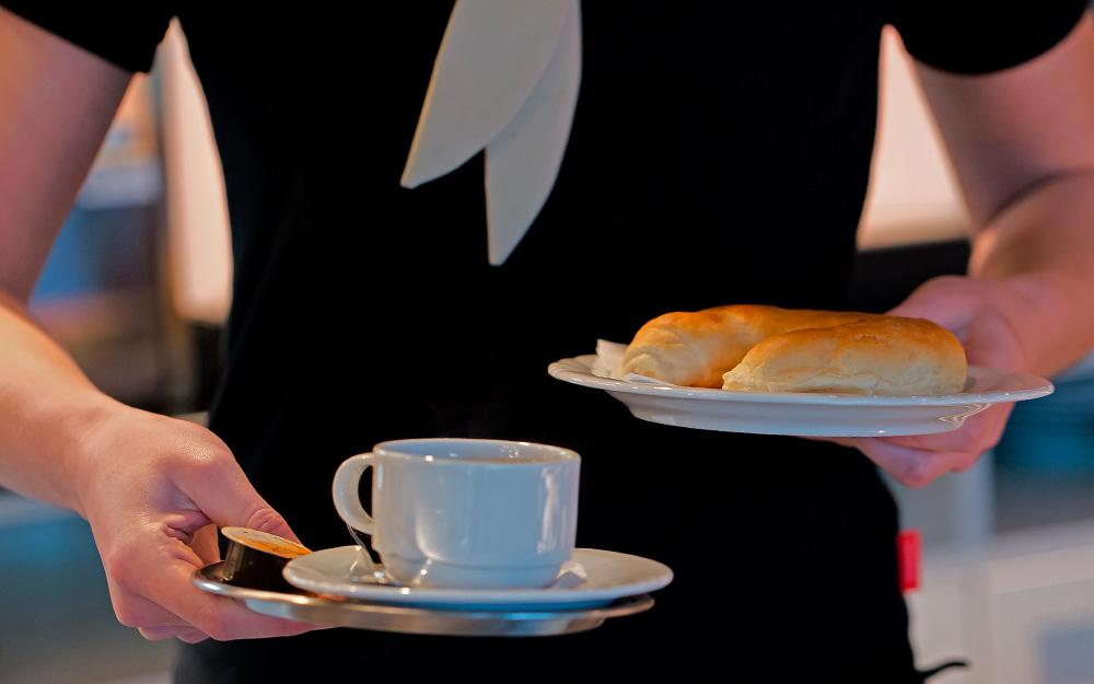 Servicekraft Aushilfe mit Kafeetasse und Teller